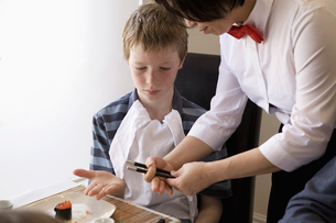 waiter showing boy how to use chopsticksの写真素材 [FYI01987451]