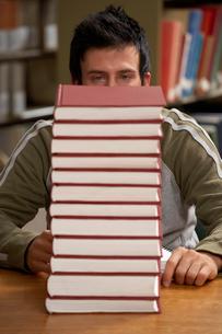 man staring at large stack of booksの写真素材 [FYI01987553]