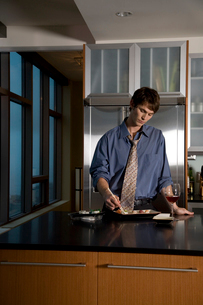 Young adult man eating sushi in kitchenの写真素材 [FYI01987583]