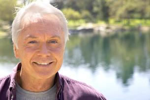Senior man standing by pondの写真素材 [FYI01987636]