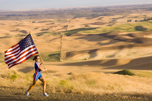 athlete with American flag on roadsideの写真素材 [FYI01987694]