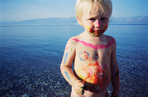 child covered in face paint by lakeの写真素材 [FYI01987701]