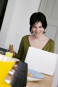 Woman eating sandwich with laptopの写真素材 [FYI01987722]