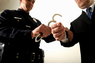 Police officer handcuffing businessmanの写真素材 [FYI01987724]