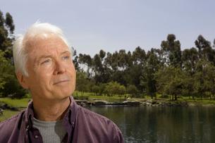 Senior man standing by pondの写真素材 [FYI01987734]