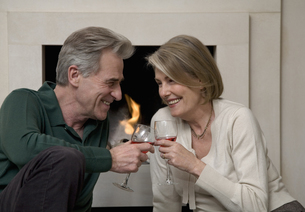 Senior couple sipping win by fireplaceの写真素材 [FYI01987778]