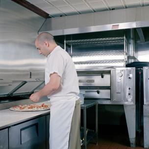 Cook making pizzaの写真素材 [FYI01987781]