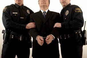 Police officers arresting businessmanの写真素材 [FYI01987789]