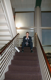 Businessman sitting at top of staircaseの写真素材 [FYI01987793]
