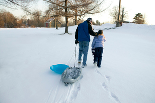 Father and daughter pulls sleds up hillの写真素材 [FYI01987797]