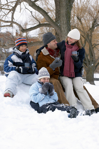 Family drinking hot chocolate in snowの写真素材 [FYI01987838]