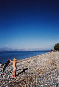 naked child with towel on rocky beachの写真素材 [FYI01987867]