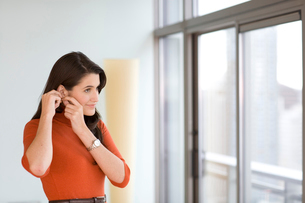 Young adult woman putting on earringsの写真素材 [FYI01987983]
