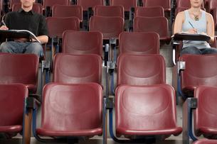 Students taking test in empty auditoriumの写真素材 [FYI01987999]