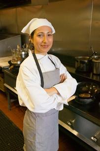 Hispanic female chef standing in kitchenの写真素材 [FYI01988049]