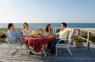 Two couples sitting on deck near beachの写真素材 [FYI01988053]