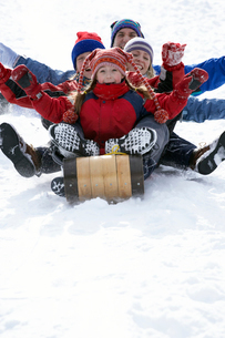 Family sledding down snowy hillの写真素材 [FYI01988127]