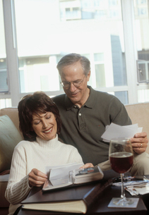 Mature couple looking at photographsの写真素材 [FYI01988171]