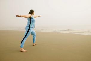 Woman practicing yoga on beach in fogの写真素材 [FYI01988183]