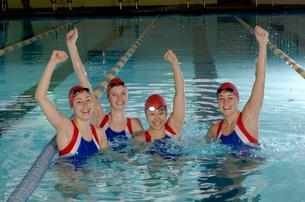 Swim team celebrating in swimming poolの写真素材 [FYI01988358]