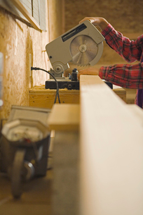 Teenage girl using circular sawの写真素材 [FYI01988375]