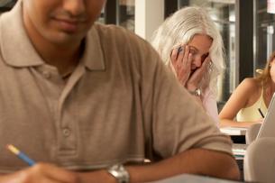 Senior female student yawning in classの写真素材 [FYI01988441]