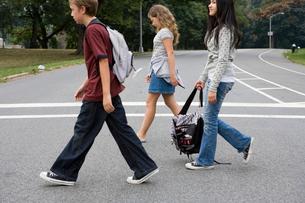 Three teenagers walk across the streetの写真素材 [FYI01988448]