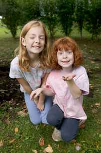 Young girls holding worm in backyardの写真素材 [FYI01988450]