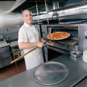 Cook removing pizza from ovenの写真素材 [FYI01988468]