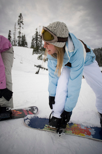 Women strapping boots to snowboardsの写真素材 [FYI01988473]