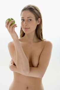 Young nude woman holding an appleの写真素材 [FYI01988532]