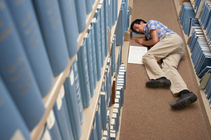 Man asleep in libraryの写真素材 [FYI01988560]