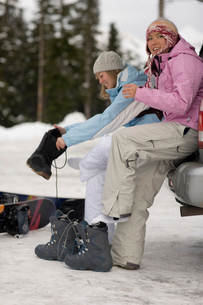 Young women putting on snowboard bootsの写真素材 [FYI01988674]