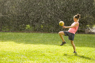 Young woman kicking soccer ball in rainの写真素材 [FYI01988733]