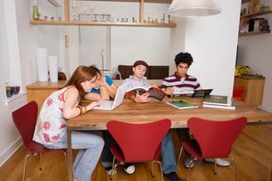 Four teenagers doing homework indoorsの写真素材 [FYI01988751]