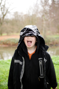 Young boy sticking out tongue in rainの写真素材 [FYI01988775]