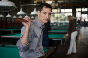 Man with pool cue in pool hallの写真素材 [FYI01988837]