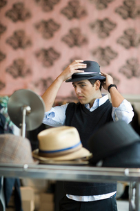 Man trying on hat in clothing storeの写真素材 [FYI01988870]