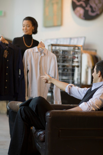 Sales clerk showing man jacket in storeの写真素材 [FYI01988880]