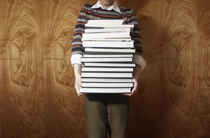 Man holding a stack of booksの写真素材 [FYI01988902]