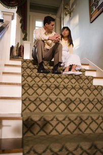 Father talking to daughter on staircaseの写真素材 [FYI01988916]
