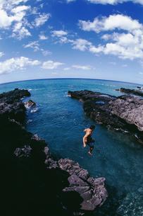 Man jumping off cliff into oceanの写真素材 [FYI01988928]