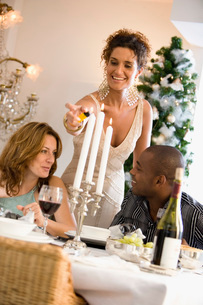 Woman lighting candles at dinner tableの写真素材 [FYI01988992]