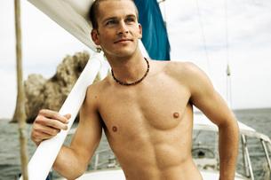 Young man balancing on sailboatの写真素材 [FYI01989067]
