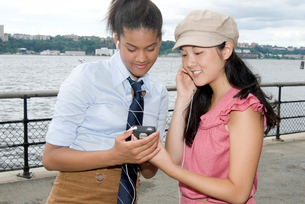 Two girls with mp.3 player outdoorsの写真素材 [FYI01989071]