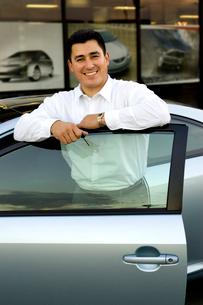 Hispanic man with new carの写真素材 [FYI01989096]