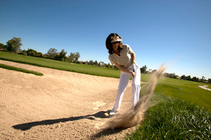Woman hitting golf ball out of bunkerの写真素材 [FYI01989123]