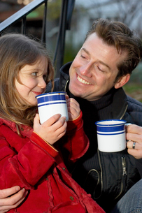 Father and daughter drinking from mugsの写真素材 [FYI01989131]
