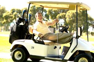 Man relaxing in golf cartの写真素材 [FYI01989144]