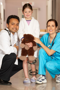 Doctor and nurse kneeling with girlの写真素材 [FYI01989201]